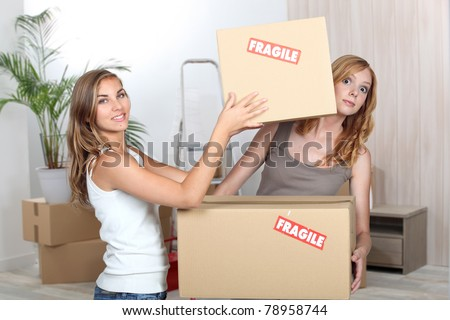 Young girls carrying boxes for moving