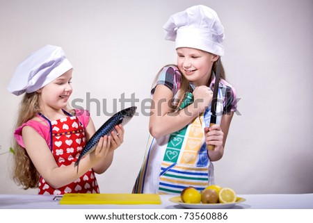 young girls cooking fish in the kitchen