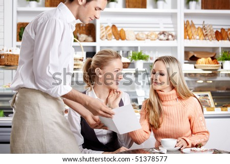 Young girls do the order to the waiter in cafe