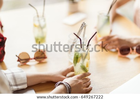 Shutterstock young girls drinking cocktails together while sitting at table in cafe, having lunch