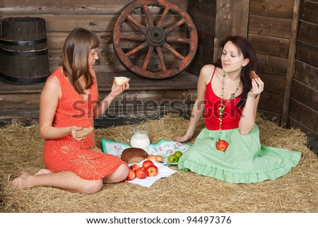 Young girls have lunch on a hayloft