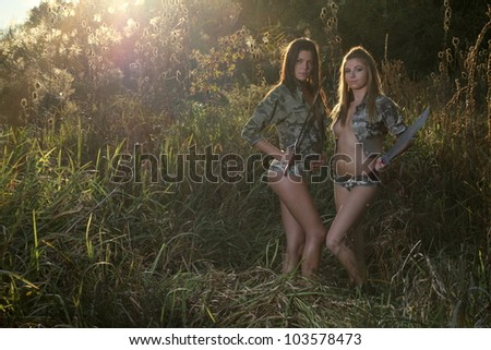 Young girls in camouflage in the forest