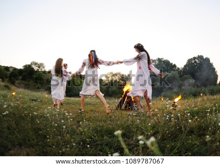 young girls in white shirts and wreaths of flowers on the background of a fire. The celebration of the pagan Slavic holiday of Ivan Kupala Day or Midsummer. ストックフォト ©