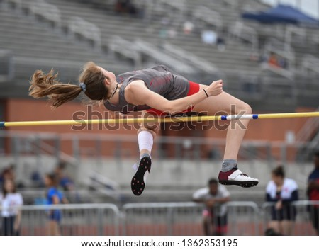 Young girls jumping high in the air during a high jump track meet