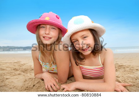 Young girls laying down at the beach