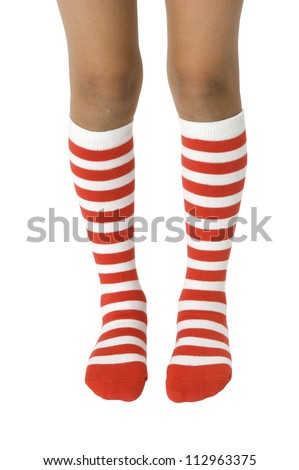 Young girls legs wearing long red striped socks on a white background. Clipping path included. - stock photo