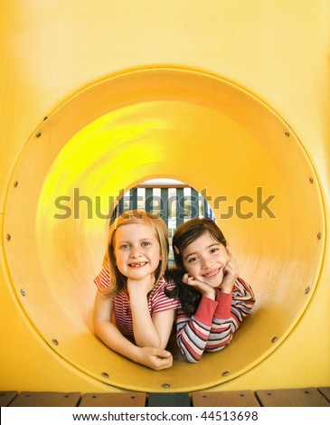 Young girls lying together in crawl tube at playground. Vertically framed shot.