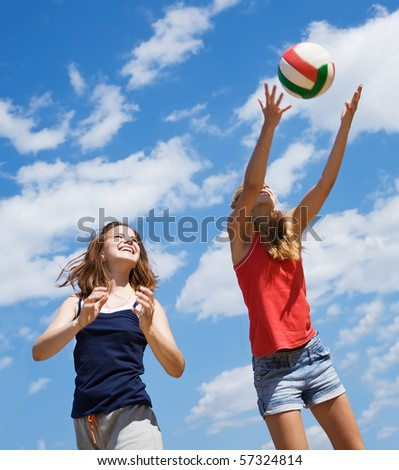 Young girls playing volleyball against blue sky