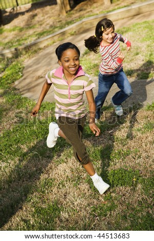 Young girls running on grass. Vertically framed shot.