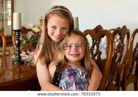 Young girls sitting at wood finished dining room table with decorations