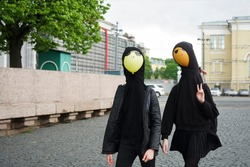 Young girls wearing black hoodie and walking at the street  with balloons under hood. no faces. Saint Petersburg, Russia.