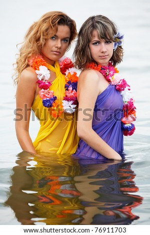 Young girls with flowers in the water