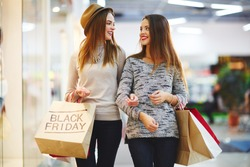 Young girls with shopping bags in store