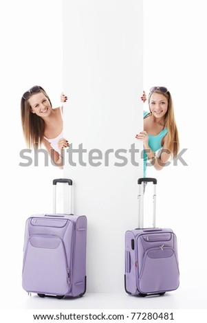 Young girls with suitcases and empty billboard on a white background