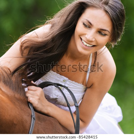Young glad brunette woman wearing white dress rides brown horse at summer green park.
