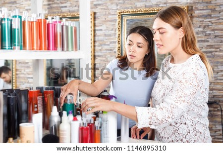 Young glad cheerful  women attentively looking hair care products at beauty salon