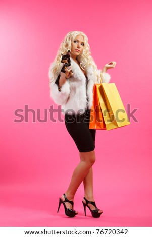 young glamorous blonde with shopping bags holding toy terrier dog against pink background