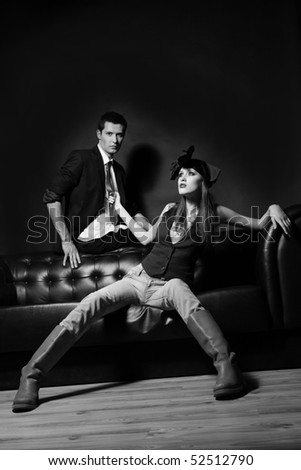 Young glamorous loving couple on a black sofa. Woman pulling man's red tie. Monochrome.
