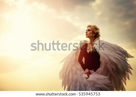 Stock Photo Young glamorous woman in a black dress with a large white angel wings on the background of a dramatic sunset sky. The concept of a fallen dark angel