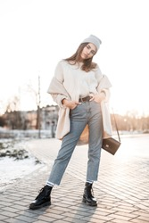 Young glamorous woman in an trendy eco coat in a gray knitted hat in stylish jeans in leather seasonal boots stands on the street on a clear day. Modern girl posing winter bright at sunset in the city