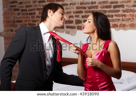 Young glamorous woman pulling a man by the red tie