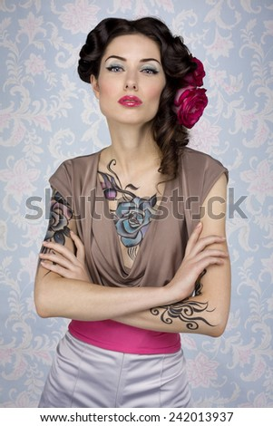 Stock Photo Young glamour attractive sexy european brunette girl with beautiful tattoo paint on her chest and arms posing for fashion photo shoot with red rose in her long hair in front of color floral background