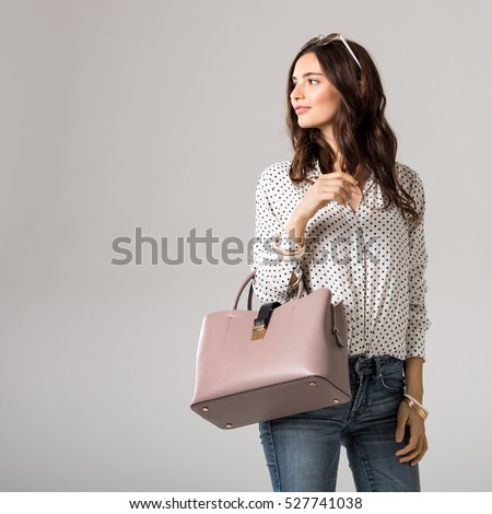 Young glamour woman wearing polka dot shirt and jeans posing with pink handbag. Beautiful stylish girl holding bag and looking away with copy space. Fashion woman holding peach bag with sunglasses.