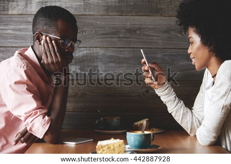 Young gloomy and bored African man getting angry while his cheerful dark skinned girlfriend chatting with her friends on social networks using mobile phone, instead of talking to him during the date