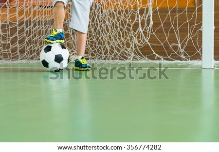 Young goalkeeper on an indoor court standing with one foot resting on the soccer ball, low angle view of his legs with copy space #356774282