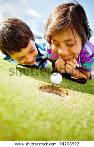 Young golf players staring at the ball to see if it goes in the hole