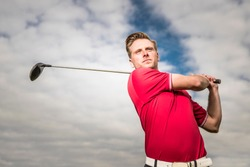 YOUNG GOLF PRO WITH RED SHIRT ILLUSTRATING A SWING ON A GOLFCOURSE WITH A BACKGROUND OF A BLUE SKY WITH WHITE CLOUDS