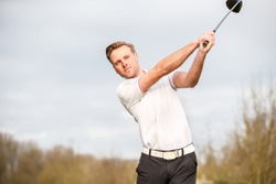 YOUNG GOLF PRO WITH WHITE SHIRT ILLUSTRATING A SWING HALF WAY ON A GOLFCOURSE WITH A BACKGROUND OF A SKY WITH WHITE CLOUDS