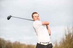 YOUNG GOLF PRO WITH WHITE SHIRT ILLUSTRATING A SWING ON A GOLFCOURSE WITH A BACKGROUND OF A LIGHT SKY WITH WHITE CLOUDS