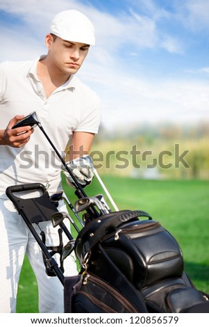 young golfer on golf course with golf bag