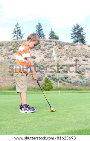 Young golfer putting his ball on the green