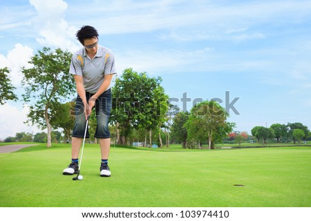 Young golfer putting on green