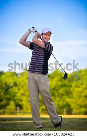 Young Golfer Swing Club under Summer Blue Sky