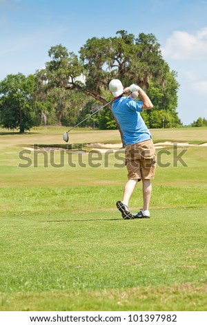 Young Golfer takes a full swing off the tee box towards the green