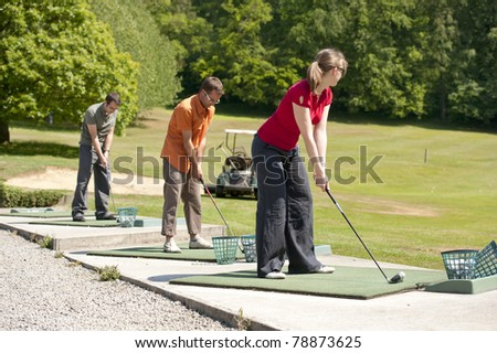 young golfers practising at the driving range