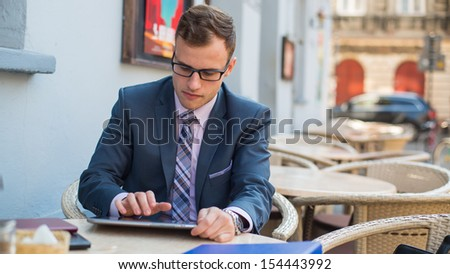 Young good-looking businessman sitting at coffee table, using tablet in cafe.