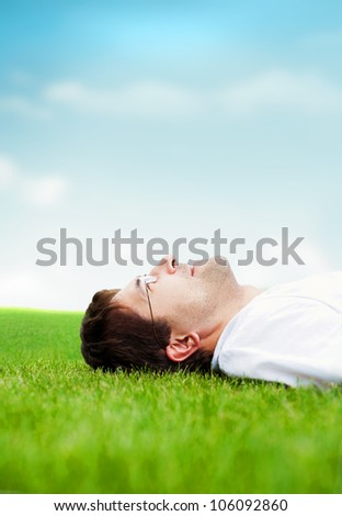 Young good looking man in white shirt lying on grass and looking at the sky - stock photo