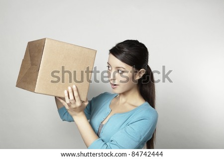 young good looking woman holding up a cardboard box