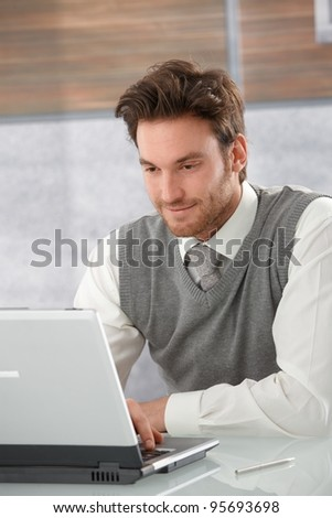 Young goodlooking casual office worker browsing internet on laptop, smiling.?