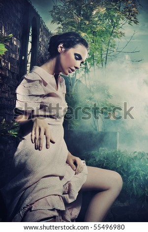 Young gorgeous brunette posing over mysterious smoky background