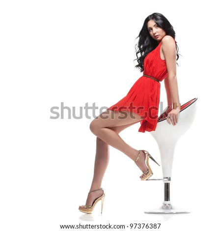 young gorgeous caucasian brunette in red dress on the chair, isolated on white, studio shot