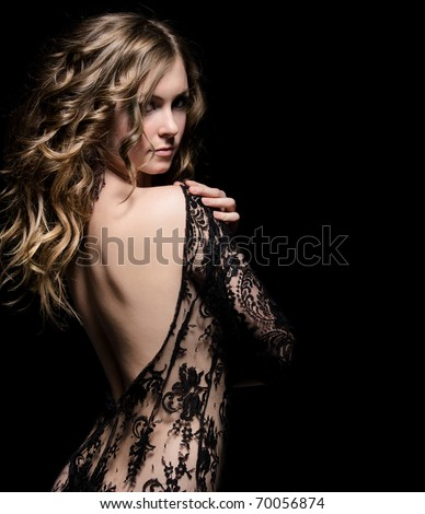 young gorgeous lady posing in lace dress, over black. space for copy