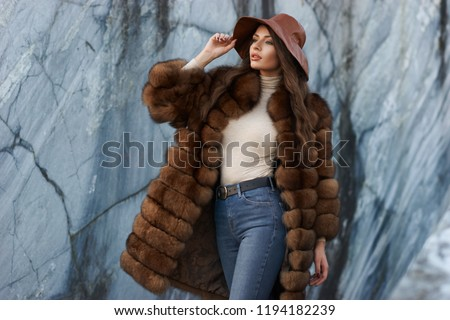 Young gorgeous woman with long wavy brunette hair in brown fur coat standing and posing against gray marble walls at stone quarry. Rich expensive woman #1194182239