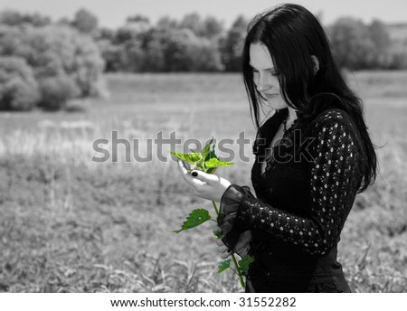 Young gothic girl with branch of nettle in hand