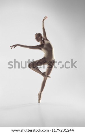Young graceful female ballet dancer or classic ballerina dancing on white studio. Caucasian model on pointe shoes #1179231244
