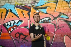 Young graffiti artist with gas mask on his neck throw his spray can against colorful pink graffiti on brick wall. Street art and contemporary painting process